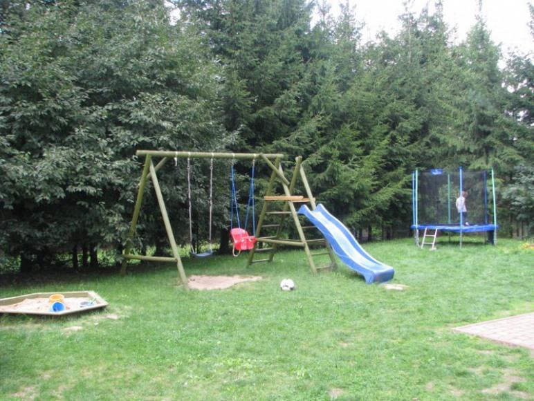 Plac zabaw do dyspozycj z piaskownicą, huśtawkami, zjeżdżalnią i trampoliną
