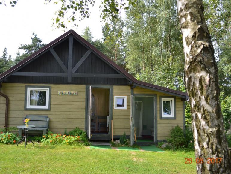 widok na domek ,w którym jest apartament z letnia kuchnią i pokój z kuchni.