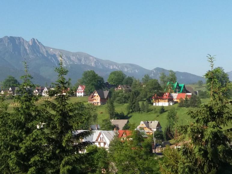 Widok na dom (zielony dach) z sąsiedniego wzgórza